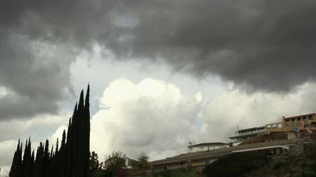 Rolling gray clouds move over hilly Los Angeles neighborhood