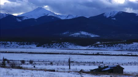 Beautiful time lapse clip of winter mountain scene turning to night with old ghost ranch and highway in the distance