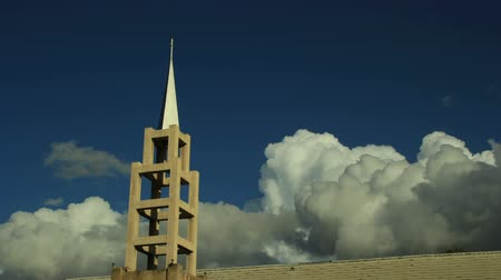 Low angle timelapse clip of protestant church steeple with large billowing clouds Stock Footage