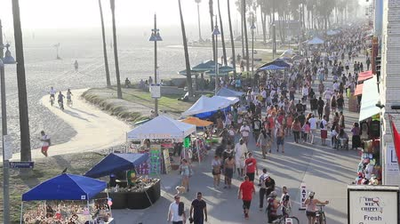 People biking, walking and performing on Venice Boardwalk Stock mozgókép
