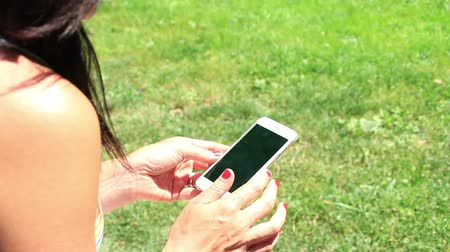 Young woman using cell phone in park