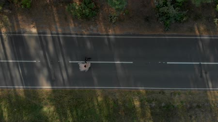 csak : Man and woman walking along the road in summer forest aerial top view Stock mozgókép