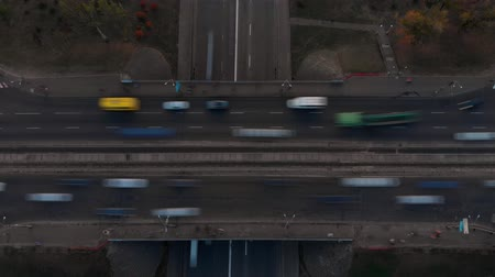 автомагистраль : Aerial timelapse of the cars passing by on a highway and a small bridge in autumn evening Стоковые видеозаписи