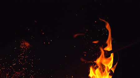 сжигание : Fire flames and a lot of bright sparks are flying from the fire at black background