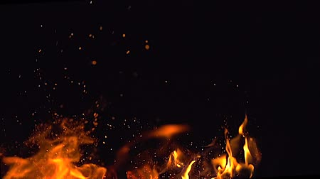 сжигание : Fire flames and a lot of bright sparks are flying from the fire at black background in slowmotion
