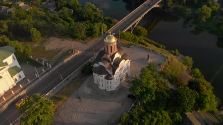 zegar : The camera circles around a small church on the river bank in a small town, Ukraine Wideo