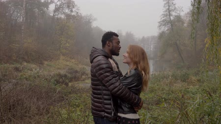 恋人 : Interracial love concept. Beautiful young interracial couple posing in the foggy autumn park, 4K 動画素材