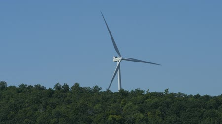 Closer up shot of a wind turbine rotating from a distance