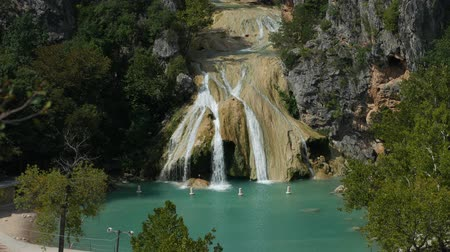 Medium wide shot of Turner Falls on a bright sunny day