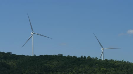 Two wind turbines rotating from a distance with hilltop in view Wideo