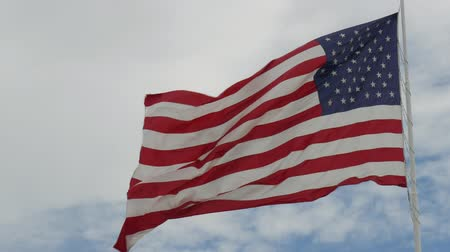 saygı : Wide steady shot of a United States flag waving in the wind, with blue and white skies in the background