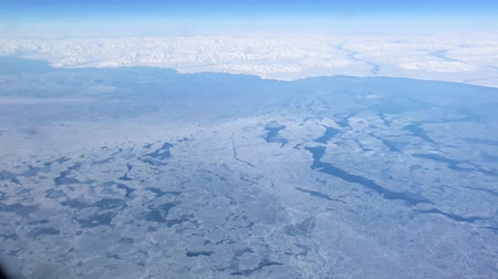 Hand-held shot of huge chunks of ice frozen over the Bering Sea in the North Pacific Ocean seen from an airplane window.