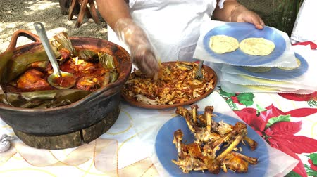 Villagers prepare a locally cooked chicken dish for tourists in a Mexican village.
