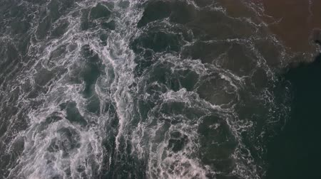 Handheld downward shot of ripples in the water created by the propeller of a ship