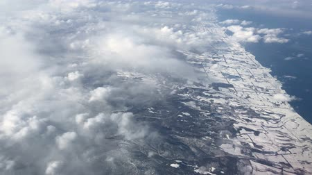 Handheld aerial shot of clouds over the snow-covered coast of Japan in winter