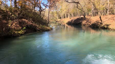 Steady shot of a blue spring with clear waters in autumn