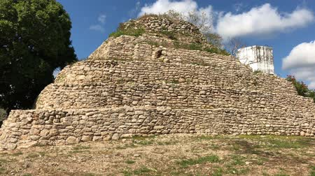 コスタ : Handheld wide shot of the ruins of a Mayan temple in a village in Mexico, with white cotton clouds in the background