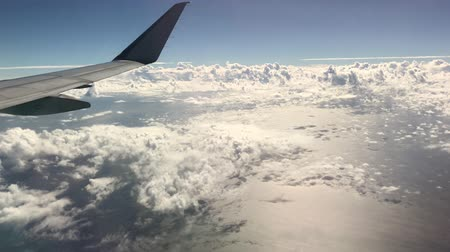 Cloud formations in skies with the tip of an airplane wing