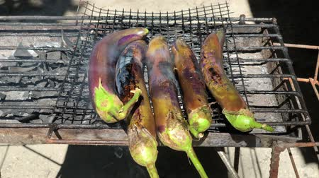 Handheld shot of eggplants grilling over hot coals outdoors