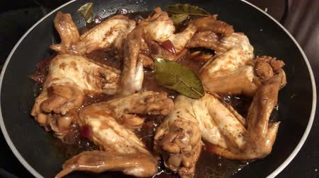 cozinhado : Hand-held shot of chicken wings frying in a pan, with sizzling sounds