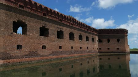 Steady shot of the ruins of an old fort reflected in the waters of the moat