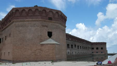 Close up of the walls of Fort Jefferson at the Dry Tortugas National Park, with people walking at the top. Стоковые видеозаписи