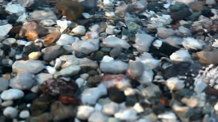 horizonte sobre a água : Shot in HD with macro focus on pebbles at the beach as the surf washes over sunset.high quality HD video footage Stock Footage