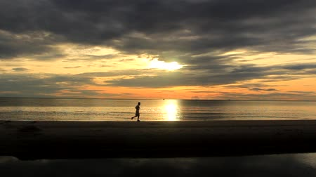 takımadalar : Hua Hin ,Prachuap Khiri Khan, Thailand - September 01,2015: Beautiful sunrise at the beach, amazing colors, light beam shining through the cloudscape over Thai gulf while a man is running Stok Video