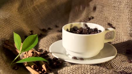 black coffee : Coffee beans falling into overflowing cup in slow motion.