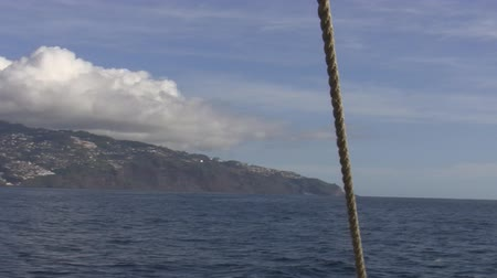 парусное судно : View from a moving sailing ship:inhabited island with mountain tops covered with clouds