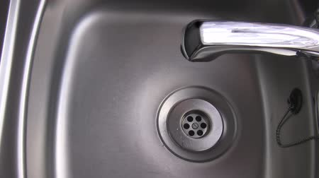 экономить : Water from the tap starts dripping slowly into the stainless steel kitchen sink Стоковые видеозаписи