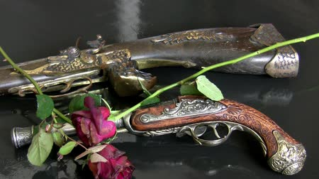batı : Close up of two retro guns on the dark grey background with withered red roses falling on them