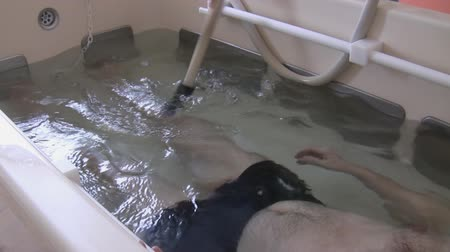 kád : A man is lying in a bath with clear water is having  recreational massage on his leg by physical therapist in a rehabilitation center centre Stock mozgókép