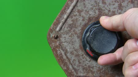 rasp : Close up of a hand turning black creaky regulator with red arrow of an old rusty machine isolated against green screen