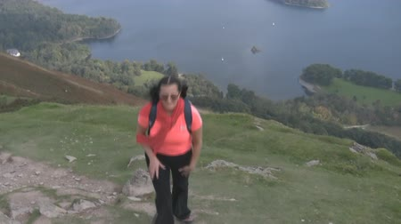 kopec :  Smiling happy dark haired woman wearing glasses in a pink t-shirt climbing last meters near the top of the mountain with a beautiful scenery behind.