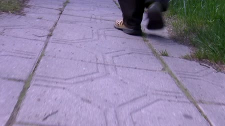 yol kenarı : Low angle handheld camera shot of tiled pedestrian path with a mans feet entering and leaving the frame.