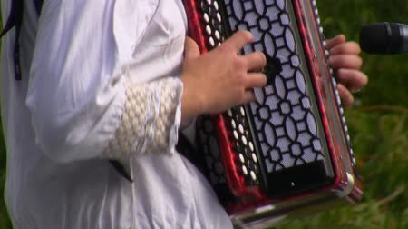kostüm : Russian Eastern European folk musician dressed in traditional clothes plays the bayan, Russian accordion on outdoor stage