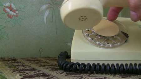 hívó : Woman hand lifts receiver and dials a long number on old white rotary telephone and hangs up Stock mozgókép