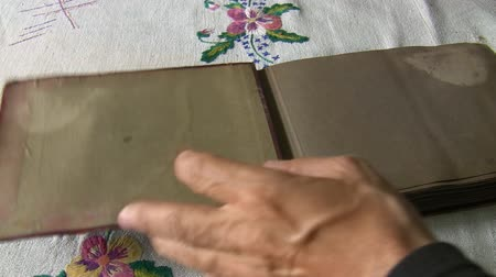 página : Red color antique photo album on the table covered with vintage tablecloth opened and pages flipping fast.