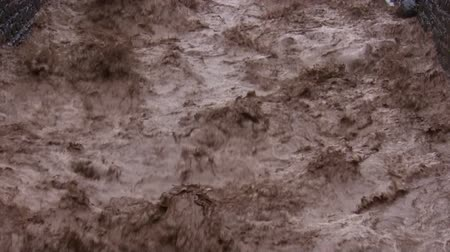 floods : Close up of rough and turbulent brown chocolate color river torrent after a flash flood. Stock Footage