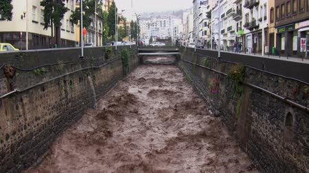 климат : Fast moving and swollen chocolate color river after a flash flood in mountains streaming down  along the streets in the city.
