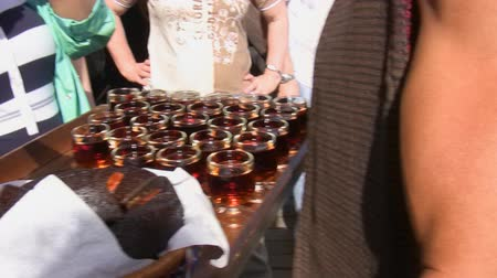 içme : Tray full of glasses of wine and pieces of cake are offered by tourist service waiter outdoors