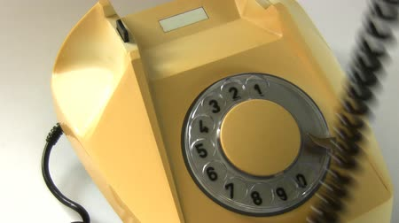 hívó : A hand lifts telephone receiver and dials an emergency number 112 on an old rotary phone and hangs up