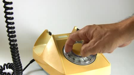 sluch : Isolated shot of a left hand of a male caller lifting an old yellow telephone receiver and the right hand dialing long number and then the caller puts the receiver down. Dostupné videozáznamy