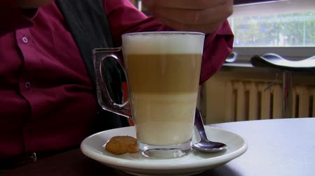biała czekolada : Man at a cafe table pouring white sugar into his coffee latte clear glass mug.
