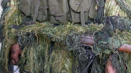 bulletproof : Close up of body of the soldier wearing masking ghillie suit with his machine gun in front
