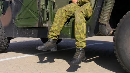uniforme : Relaxed soldier in camouflage uniform sitting in his military car Vídeos