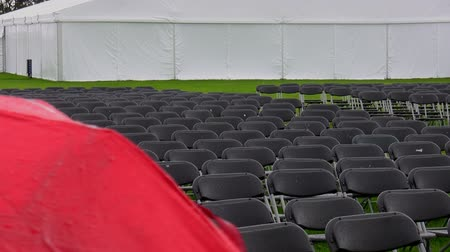 commencement : Wet and empty rows of seats at a venue outdoors on a rainy day with a part of red umbrella in front of frame. Focus on seating.