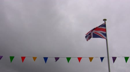 zvedák : British Union Jack flag and bunting row waving against cloudy sky