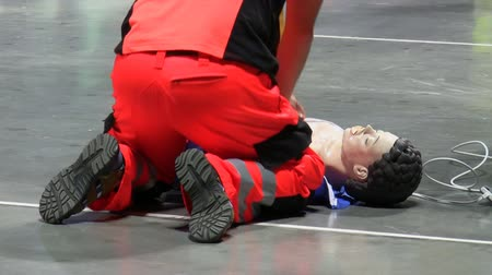 ilk yardım : Rear view of a man in a red color emergency service uniform performing cardiac massage  CPR on a dummy on the floor.